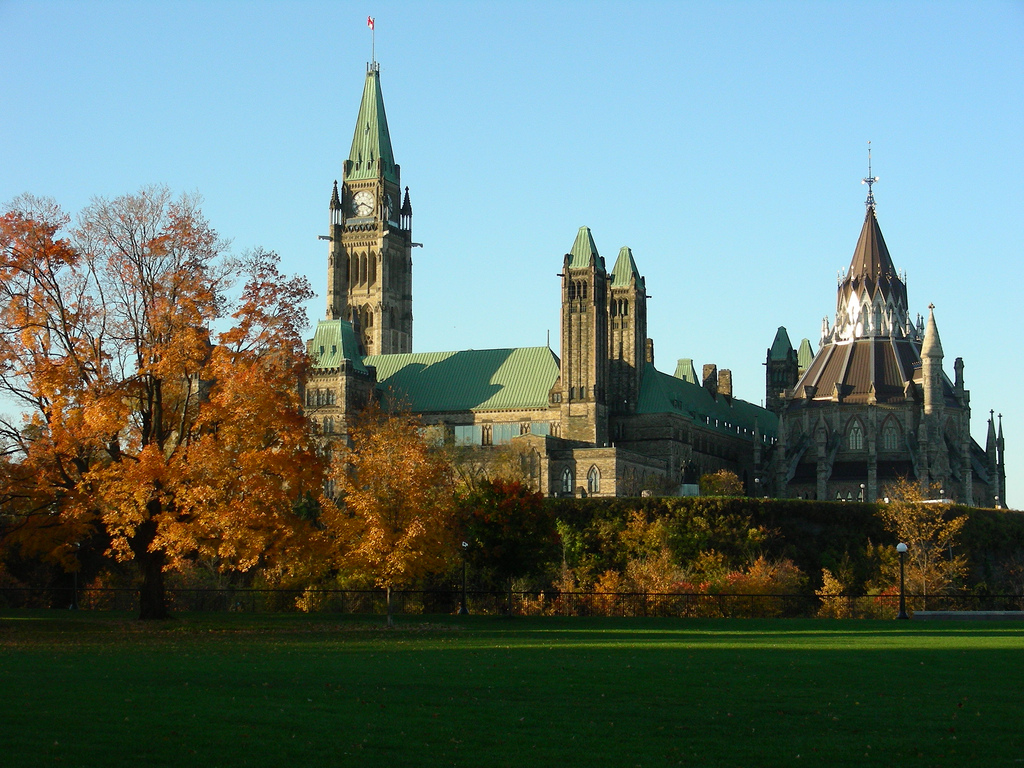 Parliament buildings surrounded by trees in fall foliage.