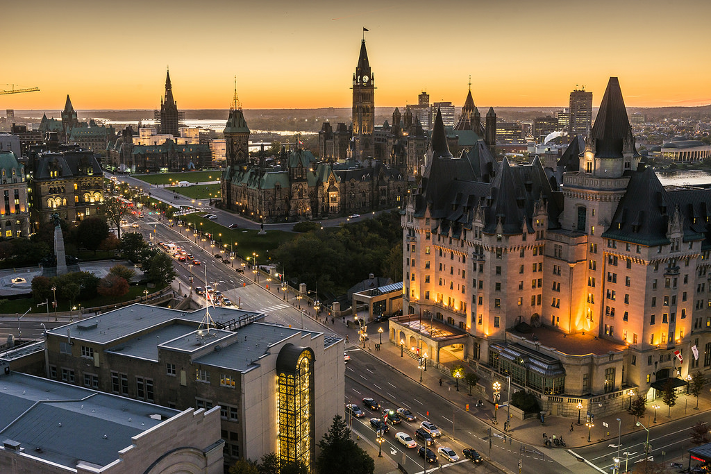 A golden sunset view of the Parliament buildings and surrounding architecture.
